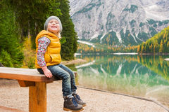 Blonde young girl sitting on picnic table at Lake Bries Stock Photo