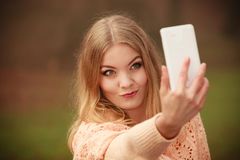 Blonde young girl taking a selfie. Photography people concept. Blonde young girl taking a selfie. Beautiful woman takes picture with mobile phone Royalty Free Stock Image