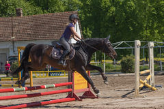 Blonde young horsewoman is jumping Stock Photos