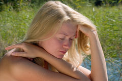 Blonde young lady. Sitting meditatively Royalty Free Stock Photos