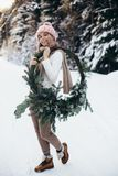 Blonde young lady with christmas wreath in winter forest. Young blonde lady in pink knitted hat hold christmas wreath with snowy winter forest on background stock photo