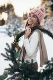Blonde young lady with christmas wreath in winter forest. Young blonde lady in pink knitted hat hold christmas wreath with snowy winter forest on background royalty free stock photo