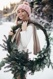 Blonde young lady with christmas wreath in winter forest. Young blonde lady in pink knitted hat hold christmas wreath with snowy winter forest on background stock photography