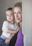 Blonde young mother and her baby boy near a wall. Beautiful family portrait about a women and a child Royalty Free Stock Photo