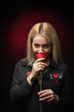 Blonde young smiling woman smelling red rose Royalty Free Stock Photography