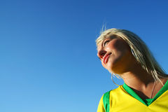 Blonde young woman. Sportive young woman with yellow shirt looking in the sun direction over a blue clear sky royalty free stock photo