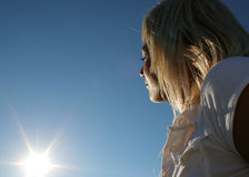 Blonde young woman. Sportive young woman with white shirt looking in the sun direction over a blue clear sky royalty free stock photography