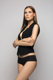 Blonde young woman in black lingerie jacket on gray background fashion and beauty Stock Photo