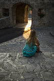 Blonde young woman in blue dress. Blonde young woman watching the reflection of the sun's rays on the floor at old town Stanjel in Slovenia Stock Images
