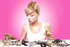 Blonde young woman choosing jewelry. Royalty Free Stock Images