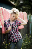 Blonde young woman in cowboy shirt and blue jeans Royalty Free Stock Photography