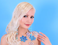 Blonde young woman decorated with snowflakes over blue Stock Photography