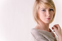Blonde young woman dressed in large white cashmere sweater. Picture present blonde young woman dressed in large white cashmere sweater Royalty Free Stock Image