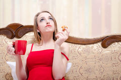 Blonde young woman drinking tea and eating cake on royalty free stock photography