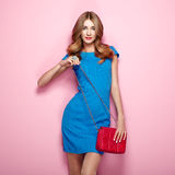 Blonde young woman in elegant blue dress Royalty Free Stock Photography