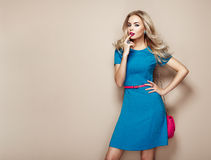 Blonde young woman in elegant blue summer dress. Girl posing on a beige background. Jewelry and hairstyle. Girl with handbag. Fashion photo Stock Images