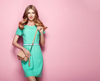 Blonde young woman in elegant green dress Stock Image