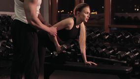 Blonde young woman exercising in gym with fitness instructor stock video