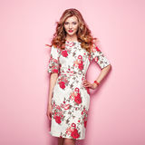 Blonde young woman in floral spring summer dress. Girl posing on a pink background. Summer floral outfit. Stylish wavy hairstyle. Fashion photo. Blonde lady Royalty Free Stock Images