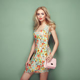 Blonde young woman in floral summer dress Stock Images