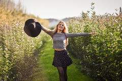 Blonde young woman happy in rural road. Portrait of blonde young woman happy with open arms in rural road. Girl wearing swater, skirt and hat Royalty Free Stock Photos