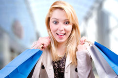 Blonde young woman holding shopping bags looking surprised downwards at copyspace in a shopping mall. Blonde young woman holding shopping bags looking surprised Royalty Free Stock Images