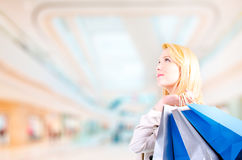 Blonde young woman holding shopping bags in a shopping mall looking upwards at copyspace. Blonde young woman holding shopping bags looking upwards at copyspace Stock Image