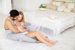 Blonde young woman hugging hispanic man and sitting near bed in morning. royalty free stock photography