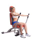 Blonde young woman on hydraulic exerciser Royalty Free Stock Photography