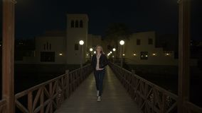 Blonde young woman in leather jacket walks alone on wooden pedestrian bridge between lamp post at night or evening. Sad stock footage