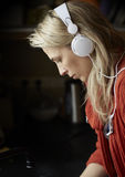 Blonde young woman listens music by headphones Stock Images