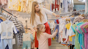 Blonde young woman with little daughter chooses kids dress in clothes store Stock Photos