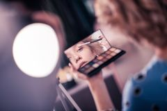 Blonde young woman looking into mirror while using eye shades stock photos