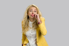 Blonde young woman making funny lips. Young business woman making funny grimace with her lips standing on grey background Royalty Free Stock Photos