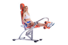 Blonde young woman on orange exerciser Royalty Free Stock Photography