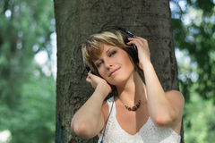 Blonde young woman in park listening to music on Royalty Free Stock Image