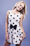 Blonde young woman in polkadot dress. Blonde Caucasian happy young woman in white and black polkadot dress with a bow Stock Image
