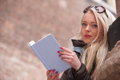 Blonde young woman reading a book outdoors Royalty Free Stock Image