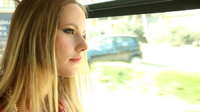 Blonde young woman, riding tram and looking out the window stock footage