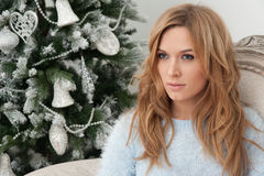 Blonde young woman sit in chair near Christmas tree Royalty Free Stock Images