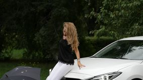 Blonde young woman sitting on the hood of the white car in summer day. slow motion stock footage