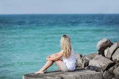 A blonde young woman sitting on a stone with her back looking at the sea.  stock photo