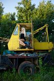 Blonde young woman sitting in tractor Stock Photo
