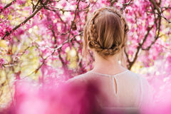 Blonde young woman standing in spring blooming garden Royalty Free Stock Image