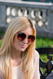 Blonde young woman wearing sunglasses. In the park Royalty Free Stock Image