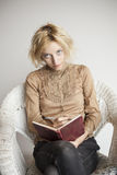 Blonde Young Woman Writing in Her Journal. Portrait of a blonde woman with blue eyes sitting in her wicker chair writing in a journali royalty free stock image