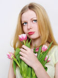 Blonde young women with pink tulips Royalty Free Stock Photography