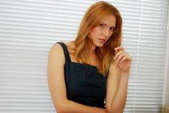 Blonde Zauber-Frau über Jalousien Stockbilder