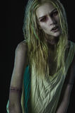 Blonde zombie woman on dark background Stock Photo