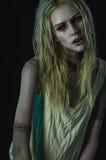 Blonde Zombiefrau auf dunklem Hintergrund Stockfoto